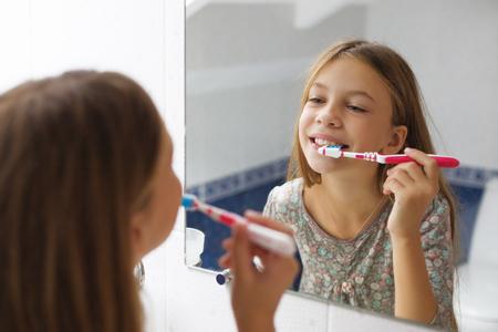 Pre teen girl brushes her teeth in the hotel bathroom Stock Photo