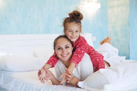 2 year old: Mom with her 6 years old little daughter dressed in winter pajamas are relaxing and playing in the bed at the weekend together, lazy morning, warm and cozy scene.