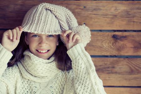 niño modelo: Linda niña de 9 años de edad que llevaba hecho punto otoño o ropa de invierno posando sobre fondo de madera Foto de archivo