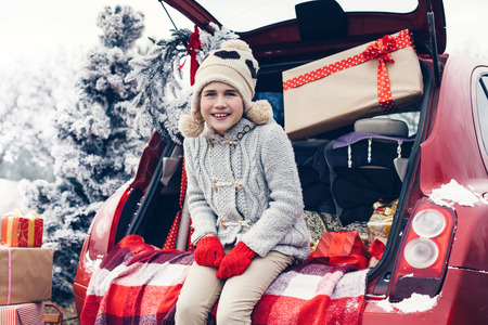 pre teen: Holiday preparations. Pre teen childr enjoying many Christmas presents in car trunk. Cold winter, snow weather. Stock Photo