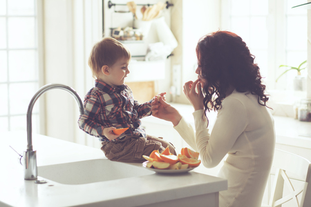 Mother with her baby eating fruits in the bright kitchen at home. Photo toned, still life.