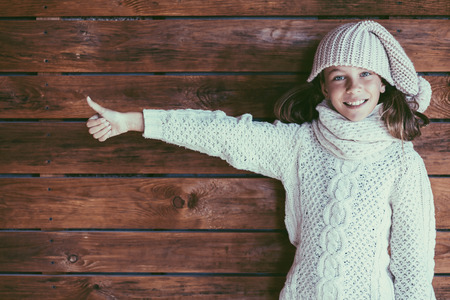 preteen model: Cute 9 years old girl wearing knitted autumn or winter clothing posing over wooden background Stock Photo