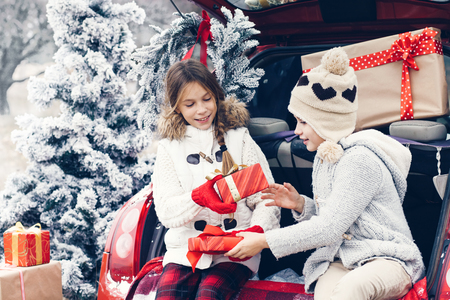 cold weather: Holiday preparations. Pre teen children enjoy many Christmas presents in car trunk. Cold winter, snow weather.