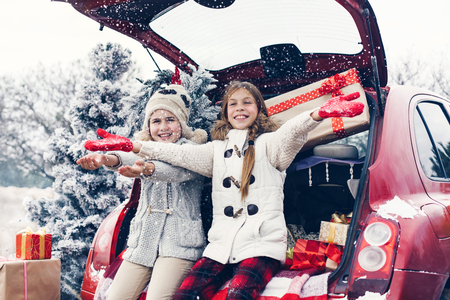 cold season: Holiday preparations. Pre teen children enjoy many Christmas presents in car trunk. Cold winter, snow weather.