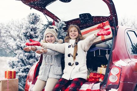 frio: Preparaciones de vacaciones. Ni�os pre adolescentes disfrutan de muchos regalos de Navidad en maletero del coche. Fr�o invierno, nieve tiempo.