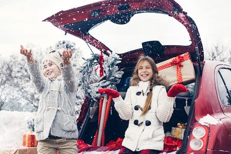 chicas de compras: Preparaciones de vacaciones. Niños pre adolescentes disfrutan de muchos regalos de Navidad en maletero del coche. Frío invierno, nieve tiempo.