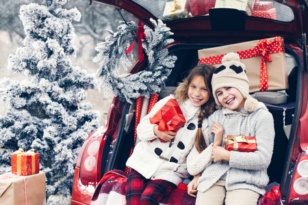 holiday trip: Holiday preparations. Pre teen children enjoy many Christmas presents in car trunk. Cold winter, snow weather.
