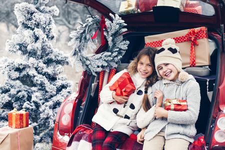 Preparaciones de vacaciones. Niños pre adolescentes disfrutan de muchos regalos de Navidad en maletero del coche. Frío invierno, nieve tiempo.