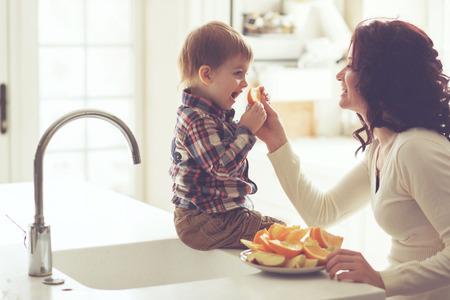 Matka z dzieckiem jedzenie owoców w jasnej kuchni w domu. Fotografia stonowanych, martwa natura.