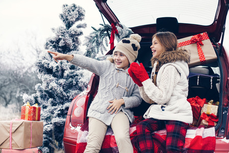 christmas shopping: Holiday preparations. Pre teen children enjoy many Christmas presents in car trunk. Cold winter, snow weather.