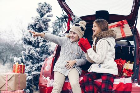 niños de compras: Preparaciones de vacaciones. Niños pre adolescentes disfrutan de muchos regalos de Navidad en maletero del coche. Frío invierno, nieve tiempo.