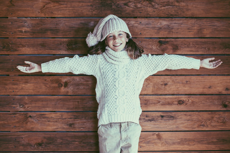 model posing: Cute 9 years old girl wearing knitted autumn or winter clothing posing over wooden background Stock Photo
