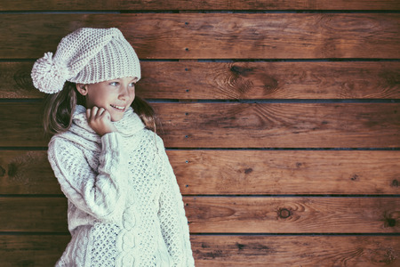 fashion: Cute 9 years old girl wearing knitted autumn or winter clothing posing over wooden background Stock Photo