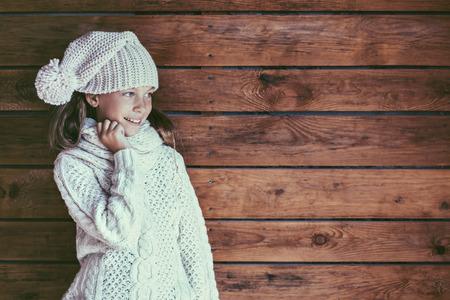 ropa de invierno: Linda niña de 9 años de edad que llevaba hecho punto otoño o ropa de invierno posando sobre fondo de madera Foto de archivo