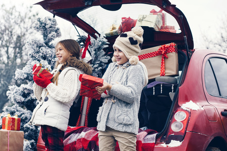 winter weather: Holiday preparations. Pre teen children enjoy many Christmas presents in car trunk. Cold winter, snow weather.