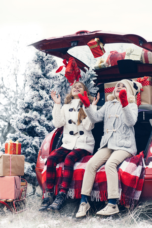 estado del tiempo: Preparaciones de vacaciones. Niños pre adolescentes disfrutan de muchos regalos de Navidad en maletero del coche. Frío invierno, nieve tiempo.