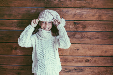 warm clothing: Cute 9 years old girl wearing knitted autumn or winter clothing posing over wooden background Stock Photo