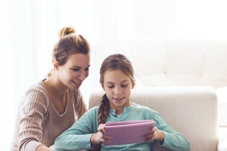 9 10 years: Mom with her pre teen daugher using ipad together Stock Photo