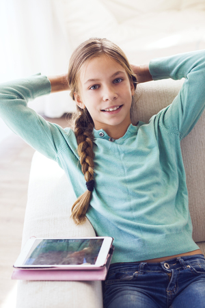 pre teens: Preteen school girl of 8-9 years old playing on  tablet pc at home Stock Photo