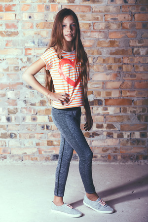 leggings: Fashion pre teen girl dressed in sports wear and sneakers posing over brick wall