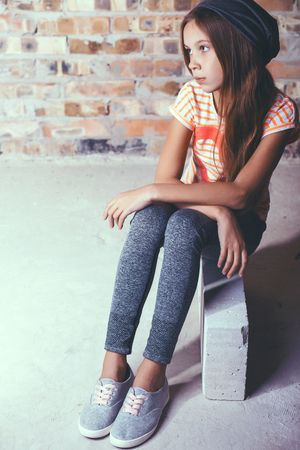 teen: Fashion pre teen girl dressed in sports wear and sneakers posing over brick wall