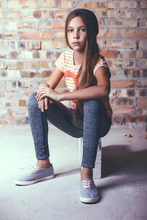 pre teens: Fashion pre teen girl dressed in sports wear and sneakers posing over brick wall