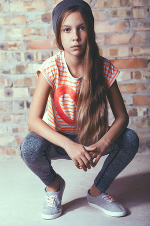 shoes model: Fashion pre teen girl dressed in sports wear and sneakers posing over brick wall