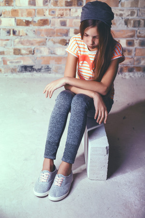 pre teen girls: Fashion pre teen girl dressed in sports wear and sneakers posing over brick wall