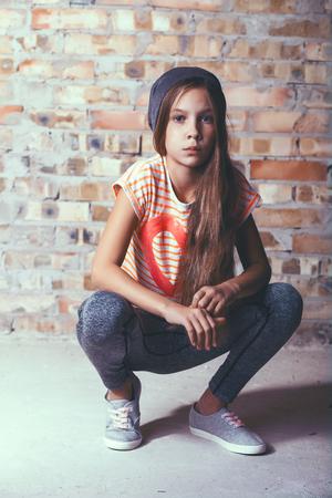 Мода предварительно подростка девушка, одетая в спортивной одежде и кроссовках, создавая на кирпичной стене