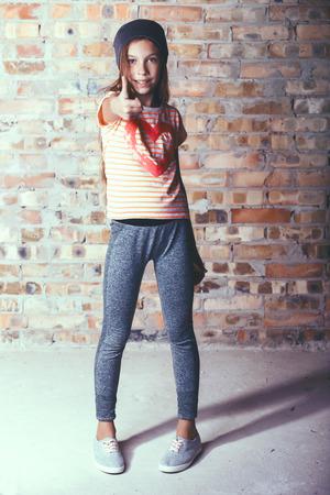 niño modelo: Moda pre adolescente vestido con ropa deportiva y zapatillas de deporte posando en la pared de ladrillo Foto de archivo