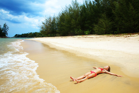 Child playing on a tropical beach during summer vacations Stock Photo