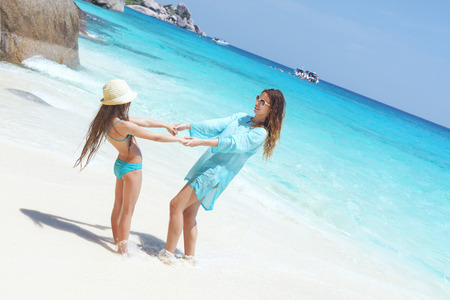 preteens beach: Mother playing with her 8 years old daughter on a tropical beach during summer vacations