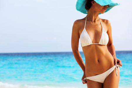 O corpo de mulher bonita no biquini sexy sobre o fundo praia