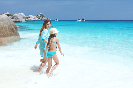 preteens girl: Mother with her 8 years old daughter resting on a tropical beach during summer vacations Stock Photo