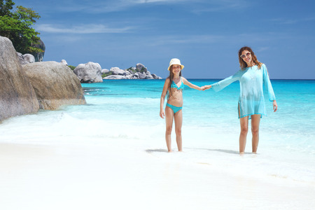 Mother with her 8 years old daughter resting on a tropical beach during summer vacations Stock Photo