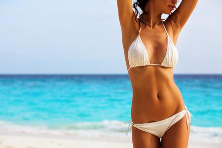 traje de baño: El cuerpo de la mujer hermosa en bikini sexy sobre fondo de playa