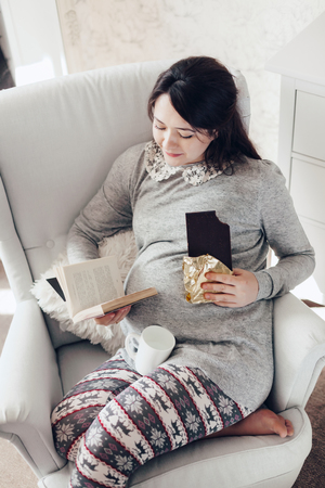 resting: Home cozy portrait of pregnant woman resting at home on a chair, reading a book and eating chocolate Stock Photo