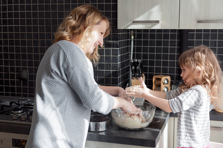 family kitchen: Mom with her 5 years old child cooking holiday pie in the kitchen to Mothers day, casual still life photo series