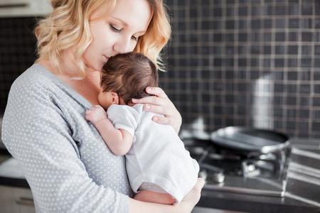 Jonge moeder houdt haar pasgeboren baby Stockfoto