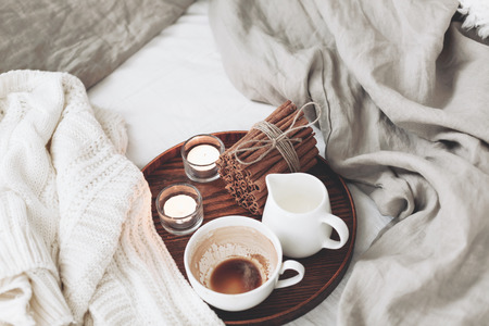 lazy: Wooden tray with coffee, milk, cinnamon sticks and tea candles in the bed, lasy morning, warm winter mood