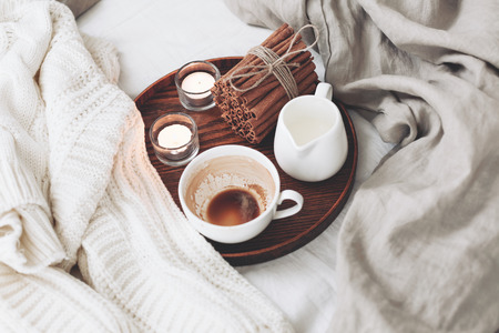 comfort: Wooden tray with coffee, milk, cinnamon sticks and tea candles in the bed, lasy morning, warm winter mood