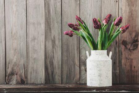 flower arrangement: Bouquet of tulip flowers in vintage vase on the shelf over rough wooden background, rustic interior decor