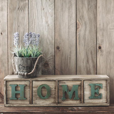 home and garden: Storage box with Home lettesr and flowers in a pot on wooden background, home rustic decor, cottage living
