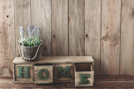 wood room: Storage box with Home lettesr and flowers in a pot on wooden background, home rustic decor, cottage living