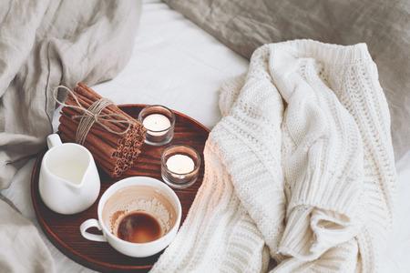 Bandeja de madera con café, leche, canela en rama y velas de té en la cama, por la mañana lasy, el estado de ánimo de invierno cálido