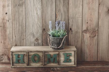 scatola di immagazzinaggio di casa lettesr e fiori in un vaso su fondo in legno, casa arredamento rustico, casa vivente