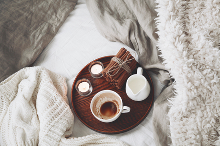 tea candles: Wooden tray with coffee, milk, cinnamon sticks and tea candles in the bed, lasy morning, warm winter mood. Top view point.