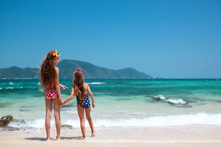 traje de baño: Dos niños jugando en la playa tropical