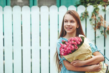 flowers garden: Tween girl holding a bunch of pink roses wrapped in craft paper over blue wooden fence