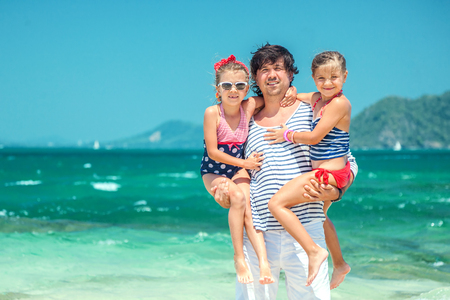 thailand beach: Dad and two his children resting at the tropical beach Stock Photo